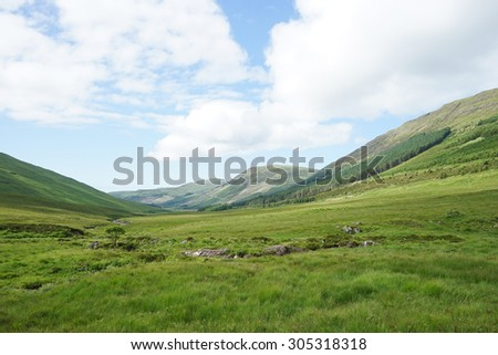 Green field and mountain with cloudy sky in the Highland.
