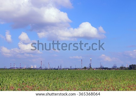 Green field and Oil Refinery with pipes and gas torch at summer sunny day - stock photo