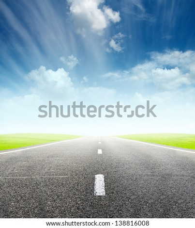 green field and road over blue cloudy sky - travel and tranportation concept - stock photo