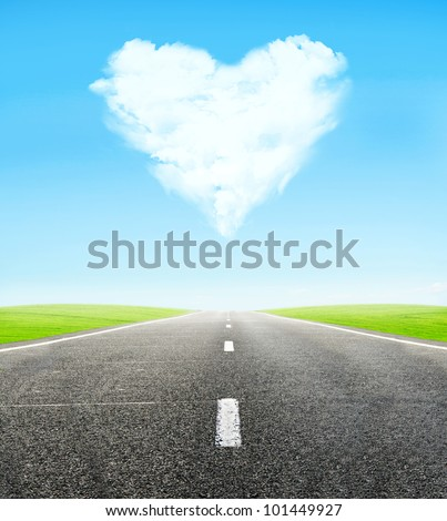 green field and road over blue sky with clouds in shape of  heart - honeymoon travel concept