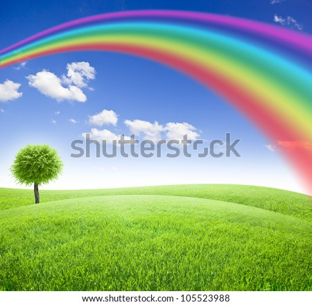 Green field and tree under blue sky with sun and rainbow - stock photo