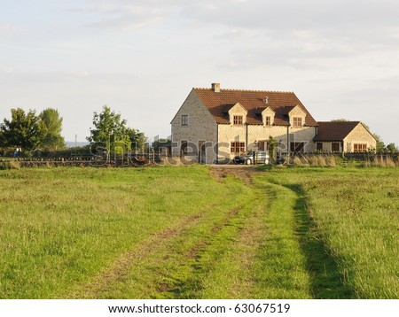 Green Field Country Lane Leading to a Farmhouse - stock photo
