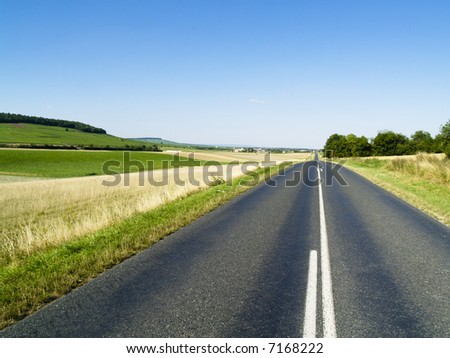 Green field, small rural route and in background village. - stock photo