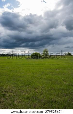 Green field, sunny clouds masive - stock photo