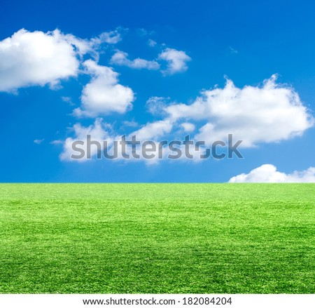 Green field under blue clouds sky. - stock photo