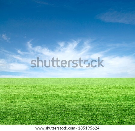 Green field under blue clouds sky.