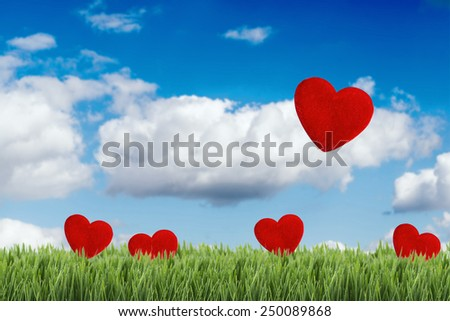 Green field under blue sky with five hearts shape on it. Love concept - stock photo