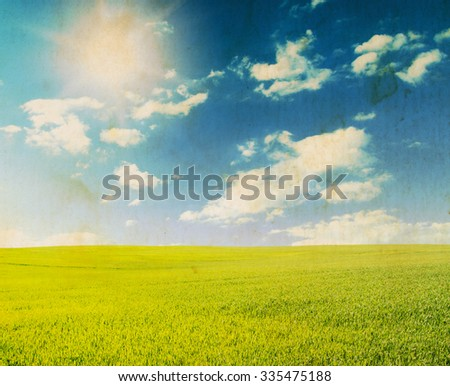Green field under blue sky with white clouds - stock photo