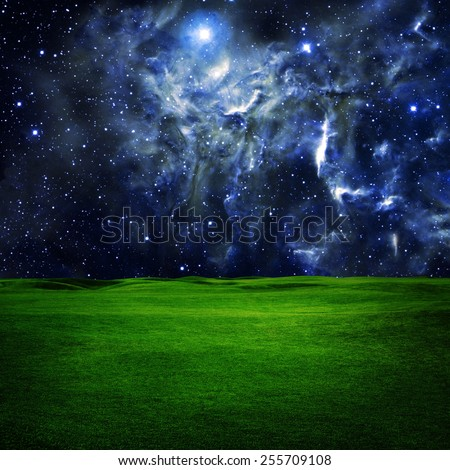 Green field under night  star sky. Beauty space nature background. Elements of this image furnished by NASA - stock photo