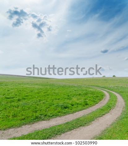green field with dirty road under cloudy sky