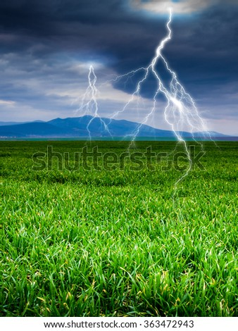 green field with storm dark clouds