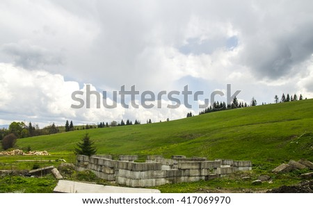 Green fields and meadows with ruins of an ancient castle. Summertime vacation sites - somewhere in Carpathian mountains (traveling to Ukraine) - stock photo