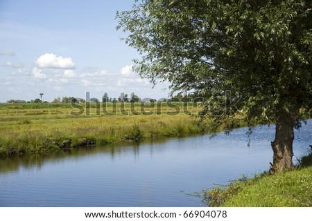Green fields, creek and windmills in famous Zaanse Schans village near Amsterdam, Netherlands - stock photo