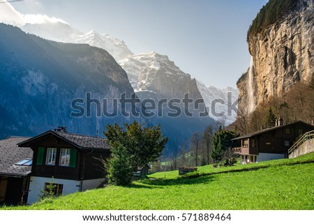 Green fields in Lauterbrunnen valley with the waterfall and the Alps in the background, Berner Oberland, Switzerland - April, 2016