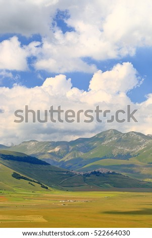 "Green fields in the ""Great Plain"" (Piano Grande) surrounded by mountains, Sibillini National Park, region of Umbria, Italy"
