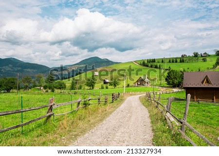 Green fields in the village with the wooden houses nearby forest in the mountains at sunny day - stock photo