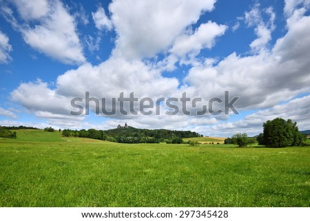 Green fields landscape with white clouds in the sky - stock photo