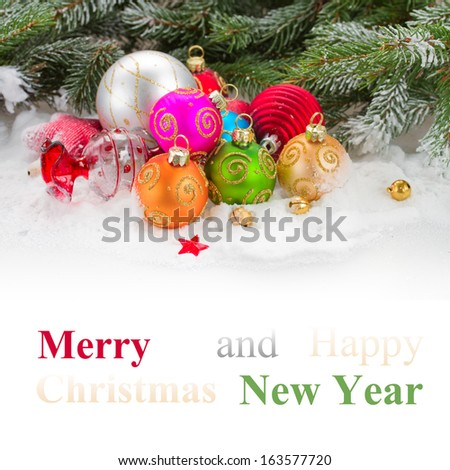 green fir tree and multicolored  christmas balls  on white snow