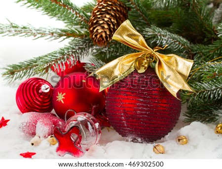 green fir tree and red christmas decorations  on snow