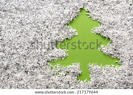 green fir tree made from background under shredded paper heap - stock photo