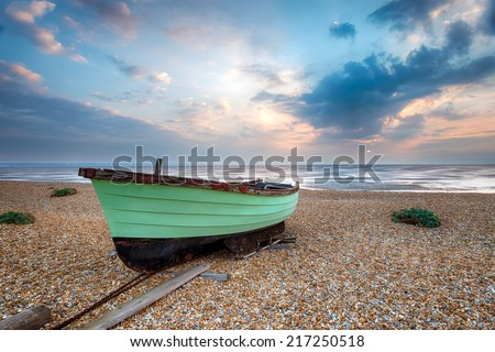 Green fishing boat at sunrise on a shingle beach at Lydd on Sea in Kent - stock photo