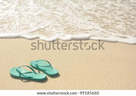 Green Flip Flops on a Sandy Beach - stock photo