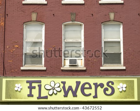 Green flower shop sign underneath three windows on a red brick building. Ontario, Canada. - stock photo