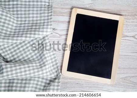 Green folded tablecloth and tablet on wooden table  - stock photo