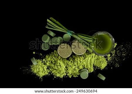 Green food supplements chlorella, spirulina, wheatgrass, pills, powder, tablets, grass blades and green juice isolated on black background, top view. Detox. - stock photo
