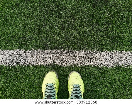 Green football boots. Green soccer boots on soccer field. - stock photo