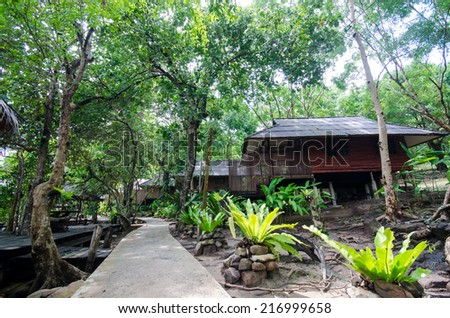 Green forest and huts in the island - stock photo