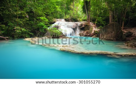 Green forest and mountain river with waterfall cascades in tropical jungle environment of Thailand - stock photo