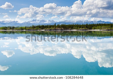 Green forested hills, snowcapped mountains and clouds at Lake Laberge, Yukon Territory, Canada are mirrored on water surface on beautiful summer day - stock photo