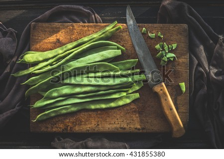 Green french beans on rustic cutting board with kitchen knife on dark wooden background, top view.  Legumes vegetables - stock photo