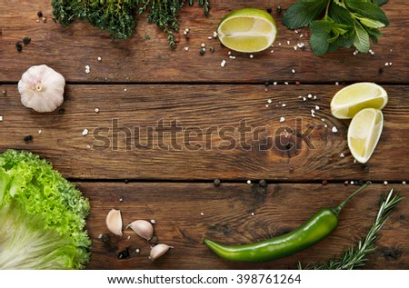 Green fresh food background on rustic wood top view with copyspace. Wood planks and vegetables, cooking ingridients flat lay. Cooking concept, lime, lettuce, garlic, chili pepper, rosemary and mint.  - stock photo