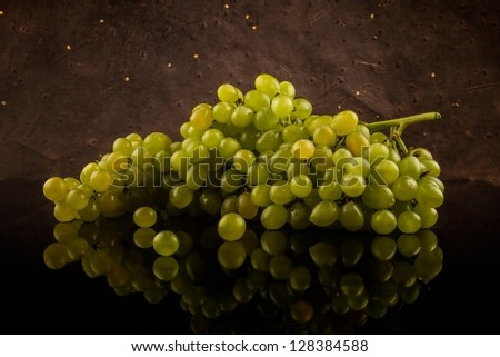 Green fresh grapes on a dark patterned background with reflectio