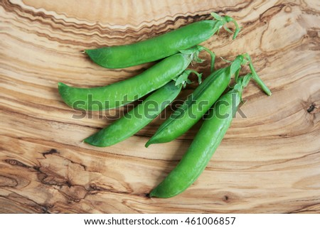 Green fresh peas on wooden background. Food theme.