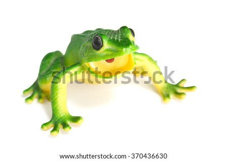 Green frog on white background. A plastic toy.
