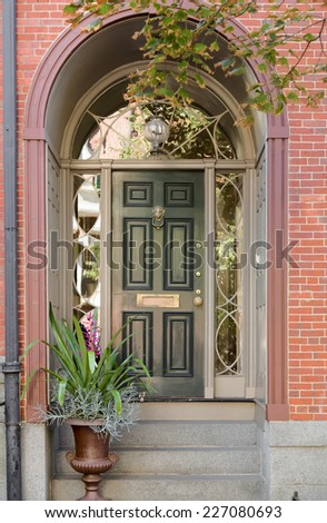 Green Front Door Under Brick Arch Entryway With Ivy And Potted Plant