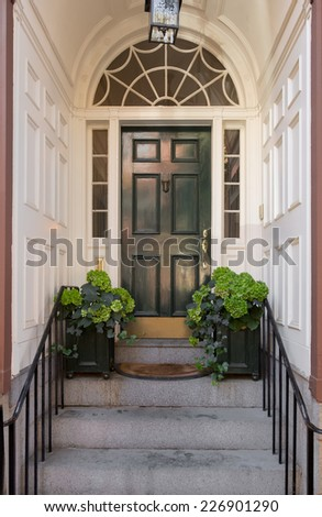 Green Front Door with Lunette and Side Windows in White Panel Arch Entryway with Greenery, Doormat and Overhead Hanging Lamp - stock photo