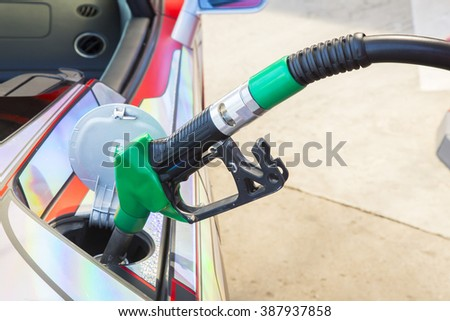 green fuel nozzle in pouring to car.