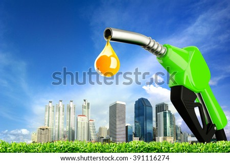 Green Fuel nozzle with city background - stock photo