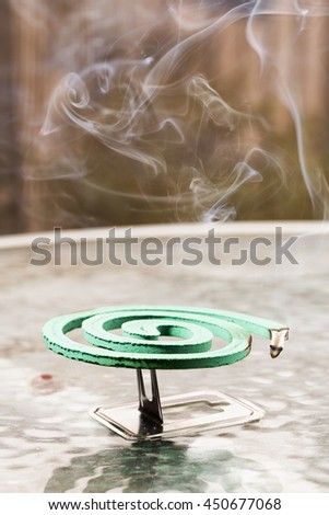 Green fumigator over glass table, vertical image - stock photo