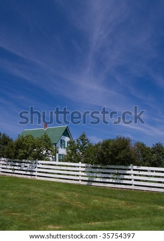 Green Gables Farm, shot below Beautiful Sky, with White Picket fence - stock photo