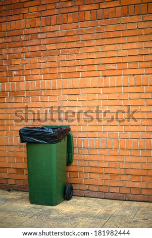 Green garbage can with plastic bag on the street - stock photo