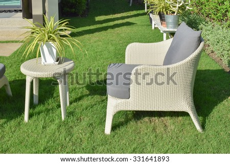 green garden with an outdoor furniture lounge group with rattan chairs, sofa and table
