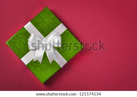 Green gift box with white ribbon on red background. - stock photo