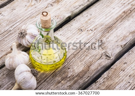 Green glass bottle with a cork lid with olive oil on a simple wooden textural background with a head of fresh garlic home. The concept is simple home cooking. Selective Focus, Horizontal - stock photo