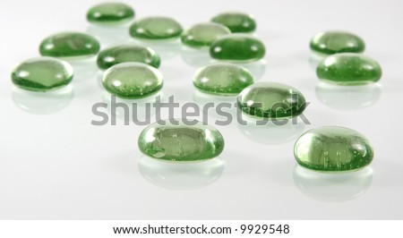 Green glass pebbles with reflection