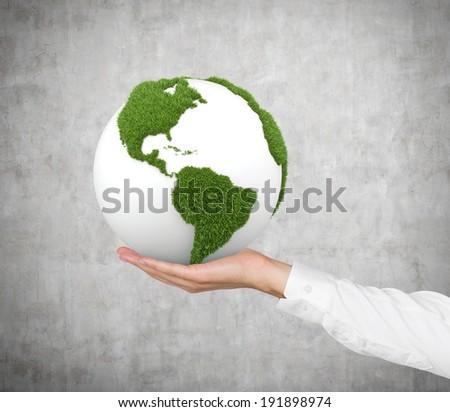 Green globe, concrete wall - stock photo